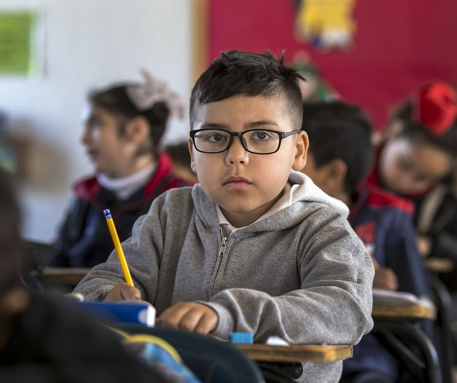 child using a school tool in the classroom