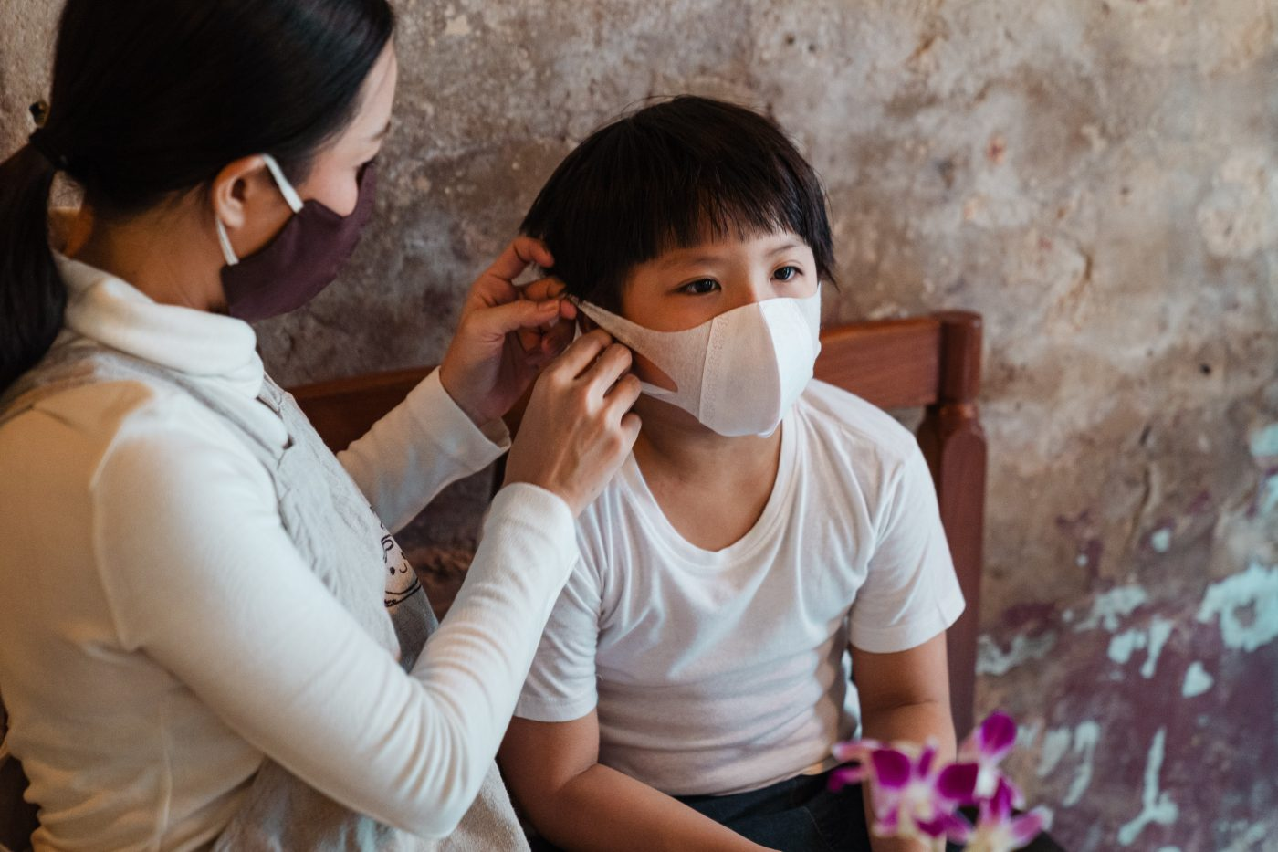 parent putting a mask on their child in 2020